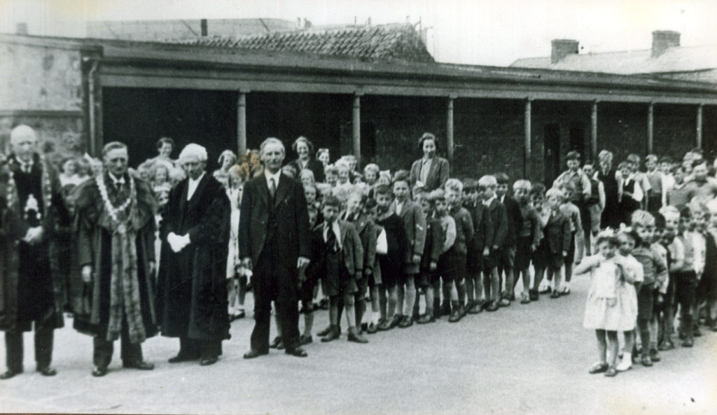 Children line up in the school playground of Spittal School in the early 1900s, with the headmaster and civic party. © Berwick Record Office, BRO 1887-50-3.