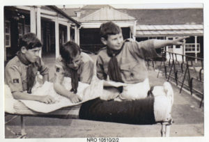 Three Scouts practising map reading on a hospital veranda (ref: NRO 10510/2/2)